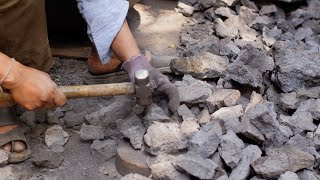 Man smashing coal with hammer into small pieces for furnace fuel