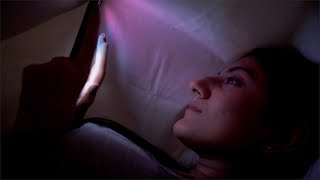 Young woman using a digital tablet at home in a dark room - technology concept