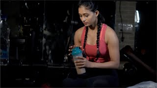 Young sporty girl drinks a protein shake after doing morning workout in a gym