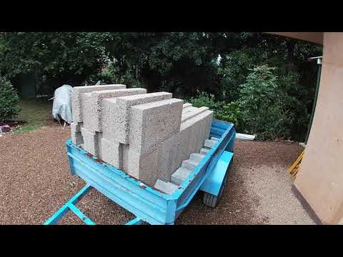 Filling the opening of a rammed earth dwelling with hempcrete blocks.