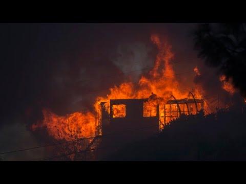 Firefighters battle heavy winds as fires burn in southern California