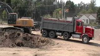 John Deere 350D excavator loading red western star tri axle dumptruck