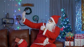 Funny Santa Claus taking selfies on his smartphone during Christmas celebration