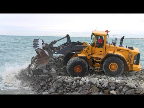 Volvo L150E Wheelloader Pushing Rocks Out In The Ocean