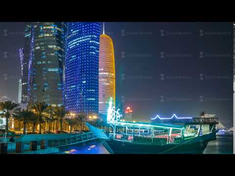Traditional dhow boat in Doha at night timelapse, with modern buildings in the background
