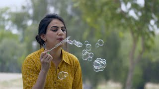 Attractive Indian woman happily blowing soap bubbles in the park - leisure concept
