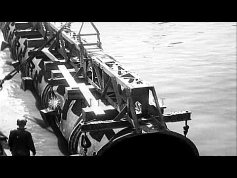 Phone lines laid and mechanics lower giant cast iron pipe into Harlem River durin...HD Stock Footage