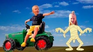 Малыш на тракторе и подружка играют в Сонную мумию. Видео для детей