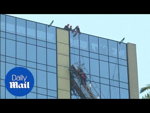 The terrifying moment Santiago window washers were rescued - Daily Mail