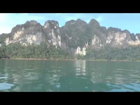 Watching the jungle laced banks of Cheow Lan Lake , Thailand from a longtail boat