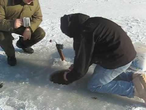 Un homme pêche un poisson aussi gros que lui
