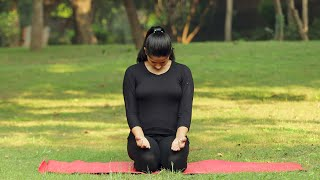 A young girl practicing purak rechak bandh pranayama outside in a park