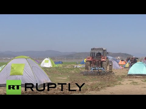 Greece: Farmer PLOUGHS land where refugees are living in tents