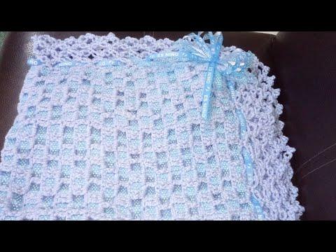 Hermosa cobija tejida a crochet decorada con listón