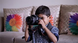 Young Indian kid clicking photographs on his digital camera DSLR - Learning photography at home