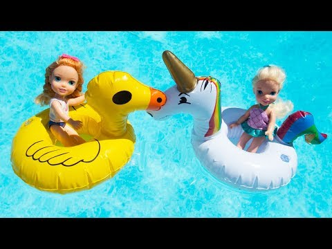 Elsa and Anna toddlers have fun in the swimming pool