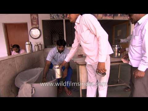 People buy fresh milk from a dairy, in Delhi