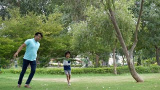 Indian father and son happily playing in a garden on Sunday weekend - family concept