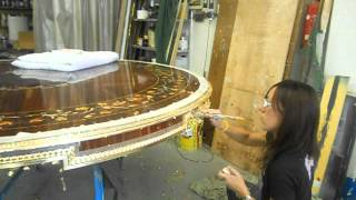Gold Leaf Being Applied In Italy To Custom Inlaid Wood Dining Table