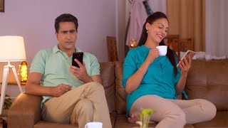 Modern day couple - Indian husband and wife busy on smartphones. Disjoint family, Social Media Impact