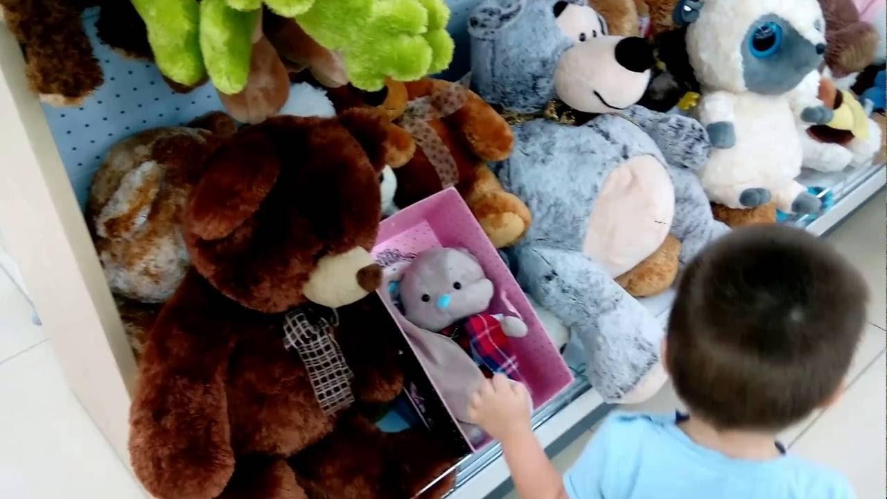 Малыш в восторге от мягких игрушек в магазине