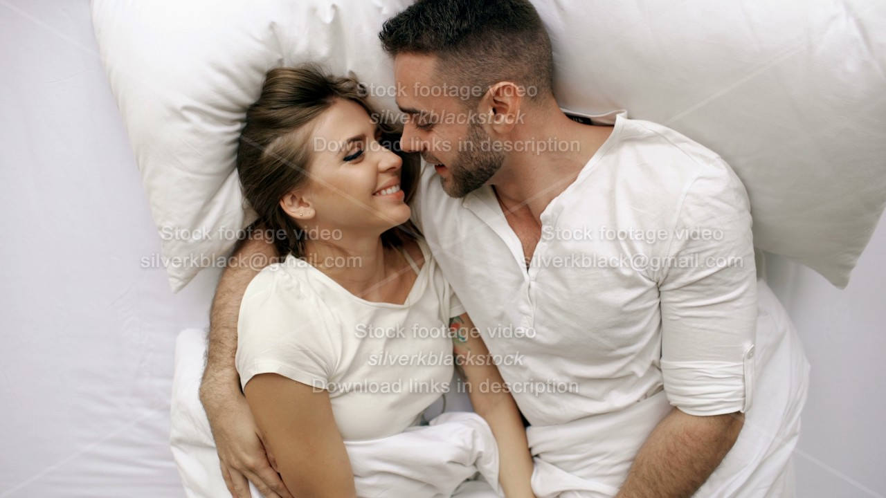 Young Beautiful And Loving Couple Talk Hug Into Bed While Waking Up In The Morning Top View Of