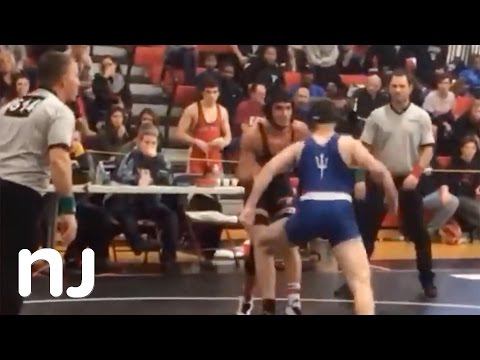 High School wrestler disqualified after punching opponent, pushing him into scorer's table