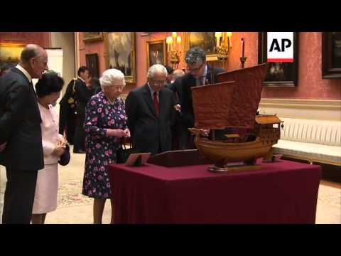 Singaporean president and Queen look at artefacts from Singapore at Buckingham Palace