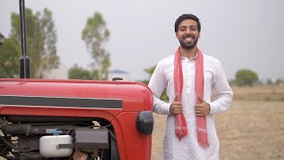 Young happy farmer happily smiling at his new red color tractor for his agricultural field