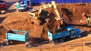 Excavator Fills Dump Trucks with Dirt at Construction Site