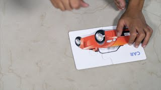 Closeup shot of a child solving cardboard car puzzle