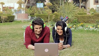 Young happy couple watching a movie together on laptop outside in a park giving various expressions