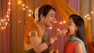 Smiling Indian mother feeding sweets to her young daughter during festivities - Happy Family