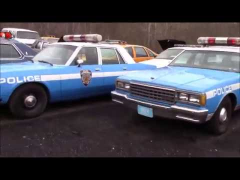 vintage-taxi-and-police-cars,-walking-a-movie-car-storage-lot.