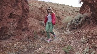 Girl Tourist in Sunglasses Goes on an Unusual Terrain Red Mountains and Red Earth As on Mars |