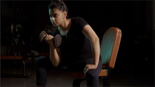 A fitness freak young Indian girl doing biceps exercises with dumbell in the gym