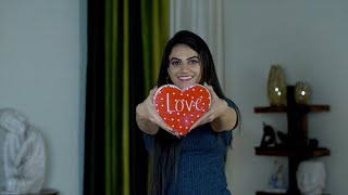 Pretty Indian girl smiling and showing a red heart symbol of love to the camera