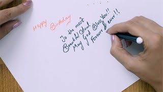 Top angle shot of an Indian girl writing birthday message for a friend on a card