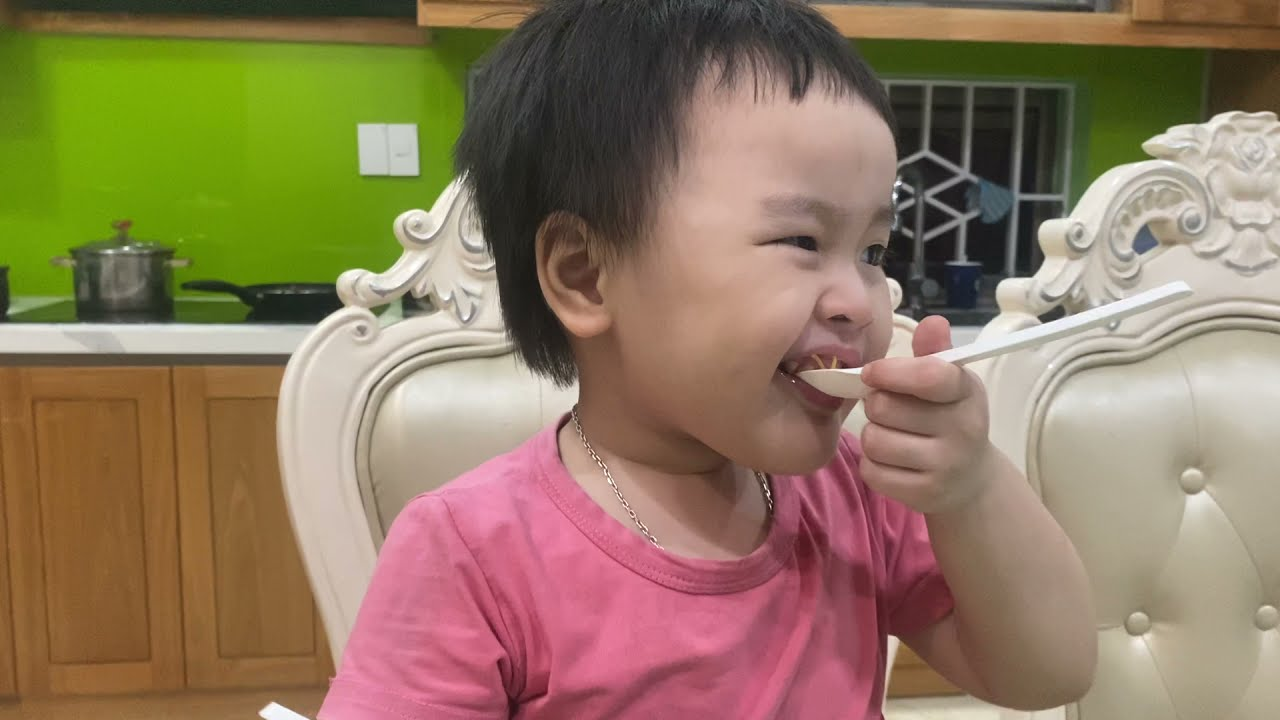 Baby cute eating  fried noodles with  mother