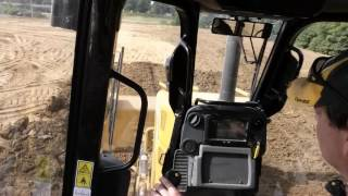 In cab view D5K CAT Dozer leveling dump truck dirt piles