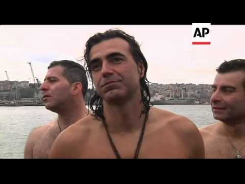 Swimmers race to retrieve wooden cross from chilly waters; mass