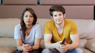 Young couple sitting together on sofa watching television and snatching remote from each other hands