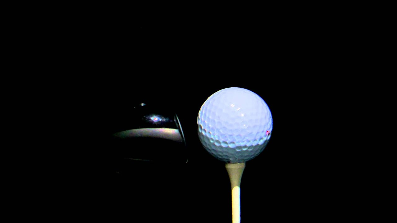Close Up Of A Golf Ball Being Hit On A Black Background
