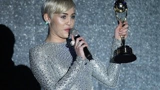 Miley Cyrus covers up in slinky silver gown to pick up two gongs at World Music Awards