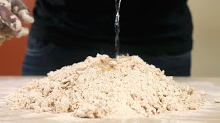 Close up shot of a man mixing water in wheat flour while kneading dough