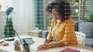 Female student girl in glasses studying at home using laptop typing writing