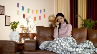 Pretty Indian girl happily talking on a phone call while sitting alone at home - leisure time