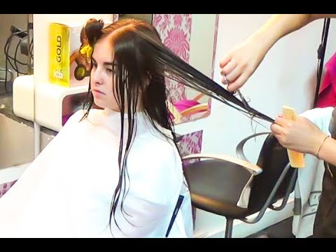 A very shy girl having an haircut from very long to medium with casual curls