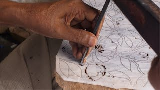 Man carving a beautiful floral design for a wooden block printing