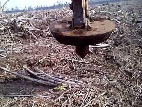 Membuat lubang tanam di lahan gambut dengan metode hole in hole menggunakan excavator